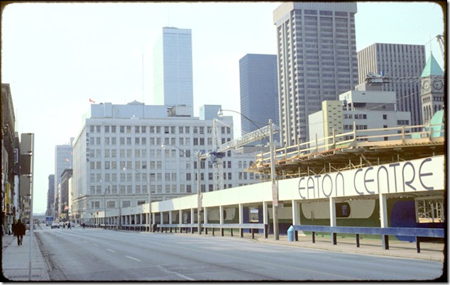 View of exterior of Eaton Centre construction site, with sign – April 18, 1975
